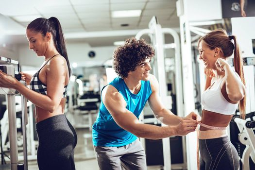 Fitness instructor measuring woman's waist before workout at the gym.