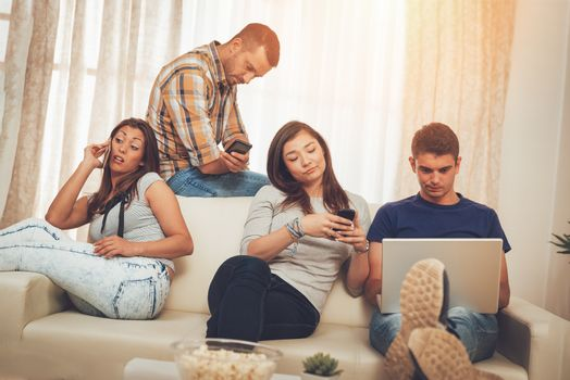 Four bored friends hanging out in an apartment and using smart phones and laptop.