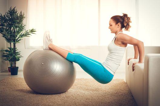 Beautiful muscular smiling girl doing pilates exercise at flat.