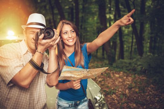 Young travelers standing before a car in the forest. Young man taking a photo with digital camera. Girl holding map and pointing destination.