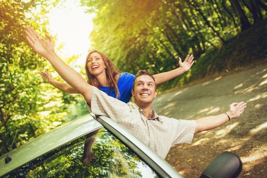 Cheerful travelers on summer travel vacation leaning out of a car window with arms raised.