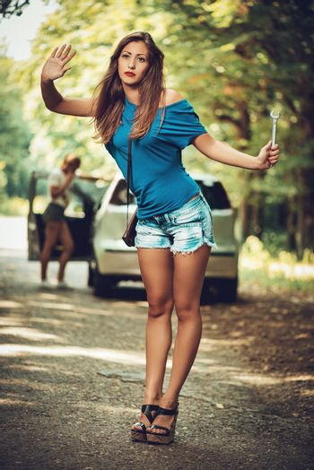 Beautiful young woman with a car that break down on the road in forest. She  is hitching and holding wrench. Selective focus. Focus on foreground.