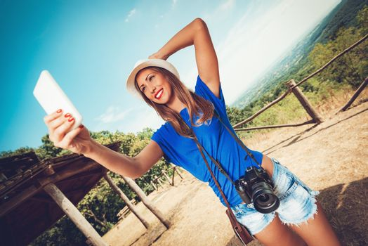 Young beautiful woman standing by viewpoint and taking selfie for memory from summer travel vacation.
