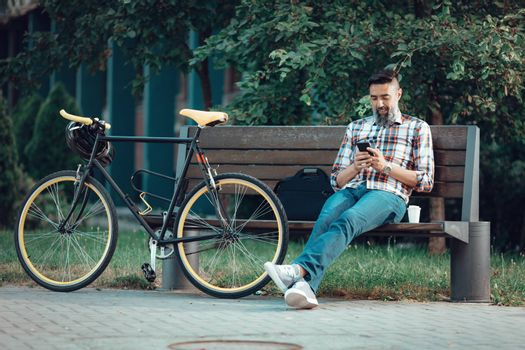 Smiling casual businessman on a break. He is sitting on a bench and using smart phone, next the bench rests a bike.