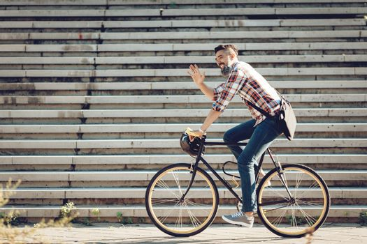 Casual handsome businessman going to work by bicycle. He is riding bike and waving Hello.
