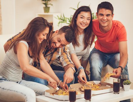 Four cheerful friends hanging out in an apartment. They are having fun and eating pizza. Selective focus.