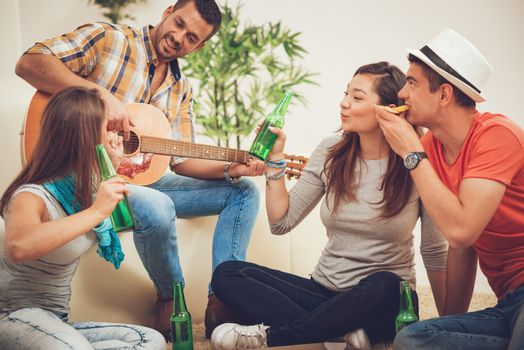 Four cheerful friends hanging out with guitar in an apartment. They are drinking beer and eating pizza.