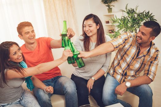 Four cheerful friends hanging out in an apartment. They are enjoying with beer and toasting together at home party.