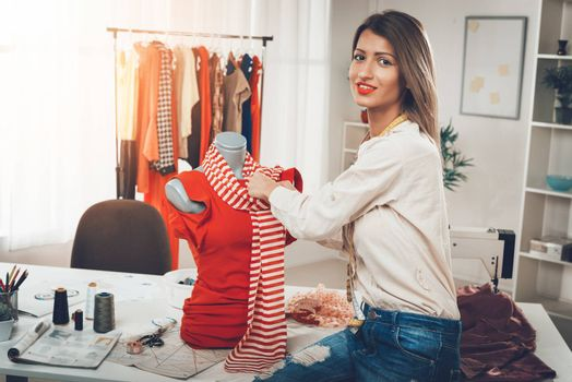 Young smiling female fashion designer creates a dress on mannequin. Looking at camera.