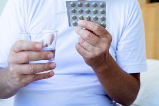 Cropped image of Sick man holding blister pack with tablets and glass of water at home. Treatment. Pharmaceutical drug. Medicine and medication.