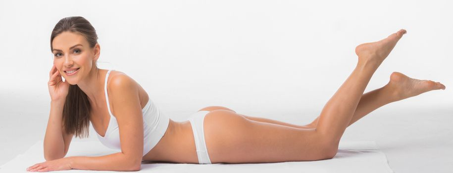Fit and sporty girl in underwear lay over white background. Sport, fitness, diet, weight loss and healthcare concept.