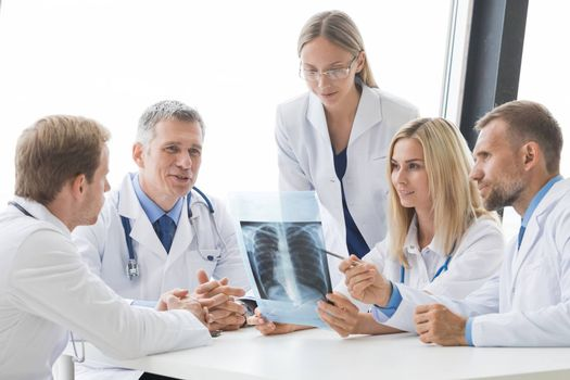 Team of experts doctors examining X-ray report on hospital office meeting