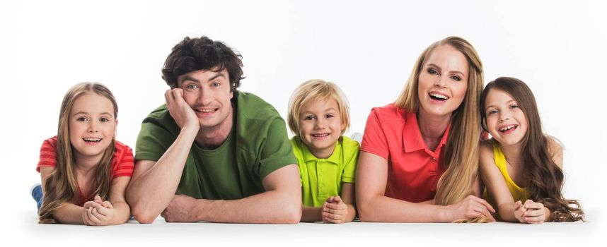Happy family of parents and three children laying on floor isolated on white background