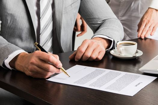Businessman in gray suit sitting at office desk signing a contract close up
