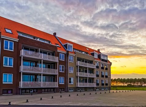apartments building with the street during sunset in Sint Annaland, touristic town in zeeland, The Netherlands