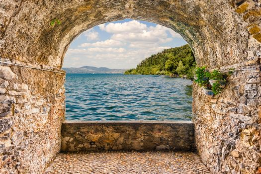 Scenic rock arch balcony overlooking Lake Bracciano from the town of Anguillara, Italy