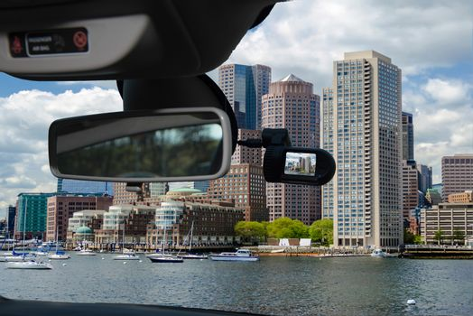 Looking through a dashcam car camera installed on a windshield with view of the Boston skyline, USA
