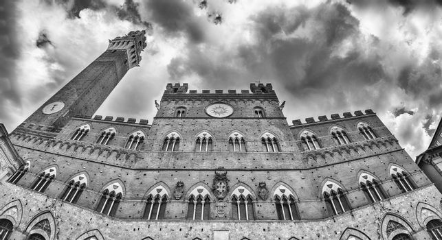 View of Palazzo Pubblico - aka Town Hall - and the Torre del Mangia medieval tower, iconic landmarks of Siena, Italy
