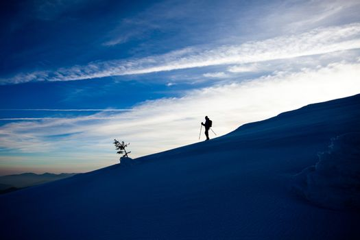 Hiker silhouette at dawn on Mount Ciucas trail in winter