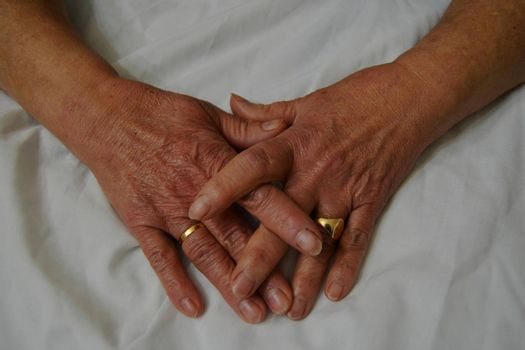 Hands of an old woman, old, clean with rings and other ornaments.