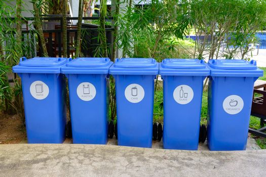 Garbage cans in different Trashcans blue color in tropical garden. Trash Garbage Disposal Classification