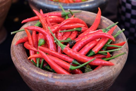 Chili peppers in clay pot red, chili peppers in Old style ceramic bowl . Top view.
