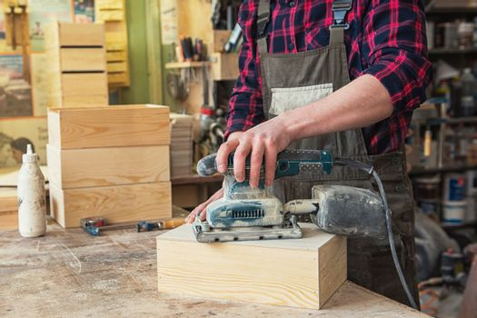 Worker grinds the wood box of angular grinding machine