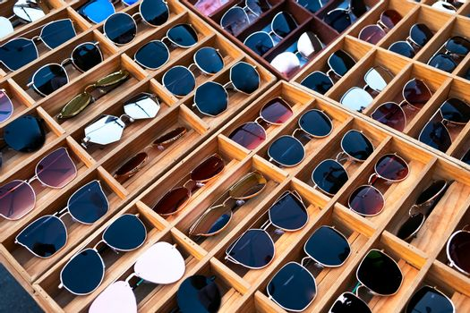 Trendy sunglasses, Summer eyeglasses, fashion collection. Collection of beautiful Different sunglasses on a stand.