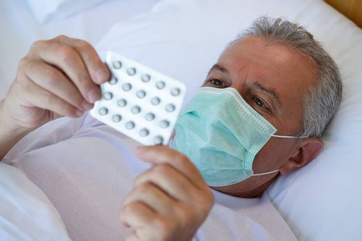 Selective focus closeup. Cropped image of Sick man in bed bed with medical face mask, taking medicines and drugs. Treatment, fever or  flu virus concept.