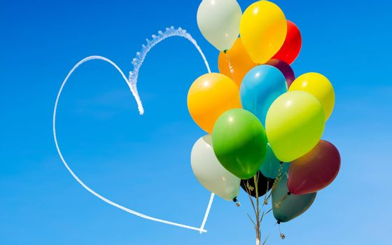 Colorful bunch of balloons and romantic heart written in the sky by an aircraft