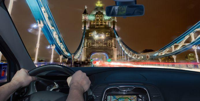 Driving a car towards Tower Bridge at night, iconic landmark in London, UK