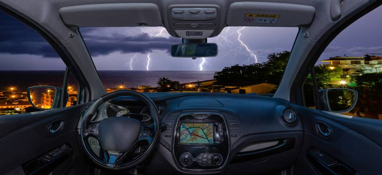 Looking through a car windshield with view over lightning storm over the sea