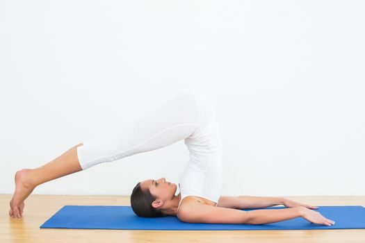 Fit woman doing the plough posture in fitness studio