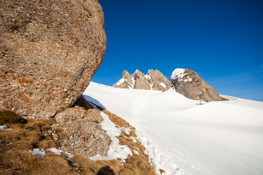 View of Mount Ciucas peak on a sunny winter day with beautiful rock formations, part of Romanian Carpathian Range