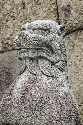 Japanese mythological feline stone sculpture over stone wall background