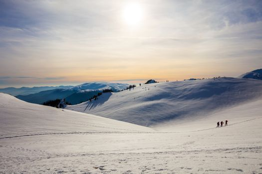 Hikers silhouette at dawn on Mount Ciucas in winter watching the sunset, part of Romanian Carpathian Range