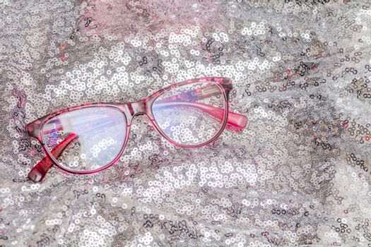 Pair of cheap reading glasses with pink frame on silver backround