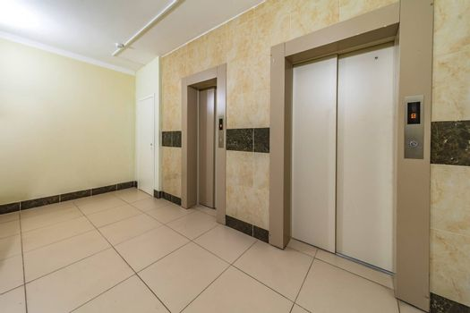empty modern elevator or lift with closed metal doors brown tile design