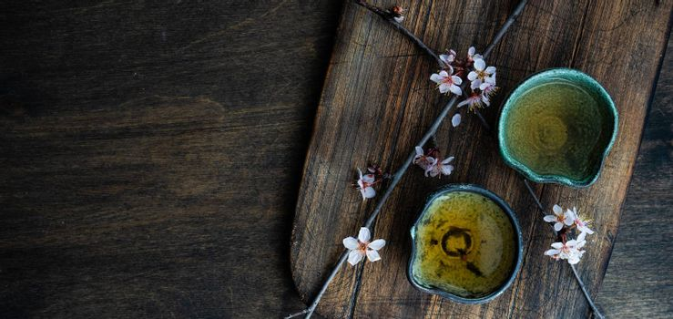 Asian style green tea set and blooming peach tree branch on wooden table with copy space