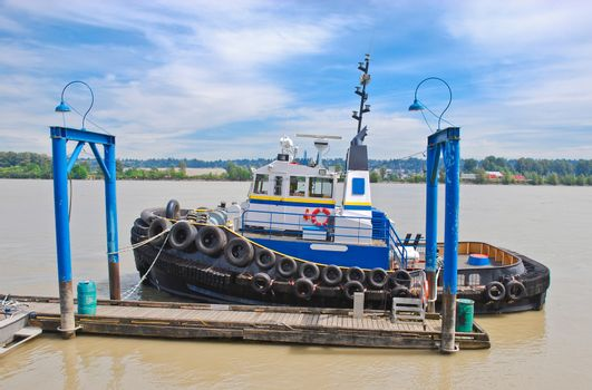 Small towboat moored at river pier on cloudy sky background
