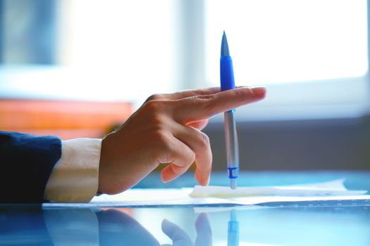 Image of human hand with pen during seminar or conference business office work concept background