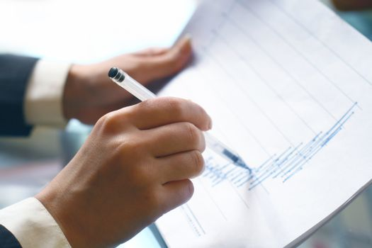 read the graph in financial report, hand pointing at graph with pen