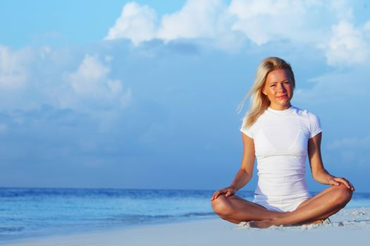 Young woman doing yoga lotus exercise outdoors on sea beach