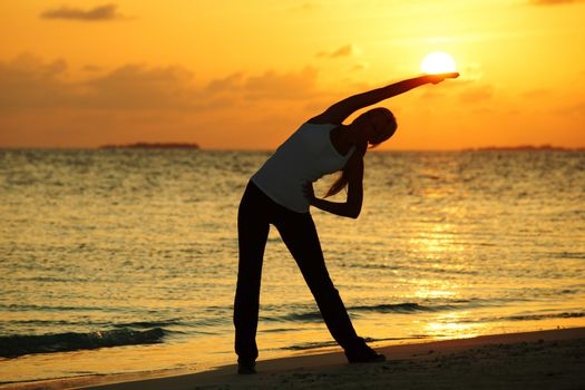 Yoga woman silhouette over sunset sky and sea background