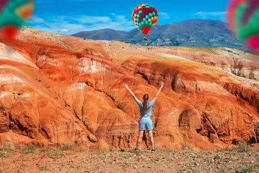 Woman in valley of Mars landscapes in the Altai Mountains, Kyzyl Chin, Siberia, Russia. Aerostat in the sky.