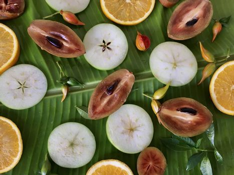 Background of fresh tropical exotic fruits on the banana leaf. Top view. Fruits sliced sapodilla, apple and orange.