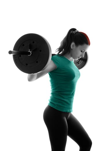 Fit attractive young woman working out with a barbell, looking down, backlit silhouette studio shot isolated on white background. Fitness and healthy lifestyle concept.