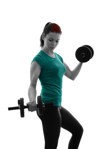 Fit attractive young woman working out with a set of dumbbells, looking down, backlit silhouette studio shot isolated on white background. Fitness and healthy lifestyle concept.
