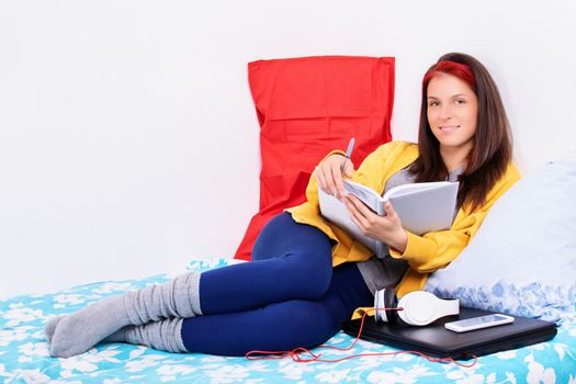 Beautiful young woman sitting comfortably on a bed in her bedroom holding a notebook, smiling and looking at the camera. Smiling girl relaxing in bed and making schedule for tomorrow.