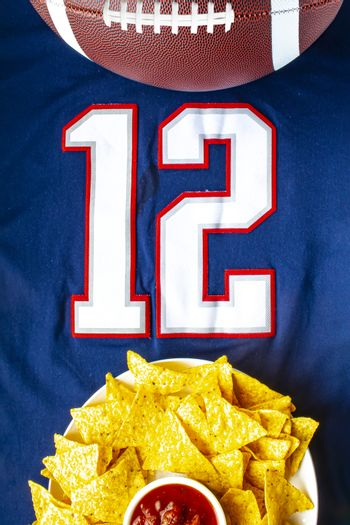 An American football with organic nacho chips and mild salsa on a white blue football jersey with the 12 number on vertical view